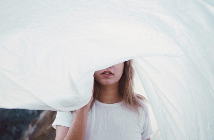 Kvinde med sengetøj foran øjnene