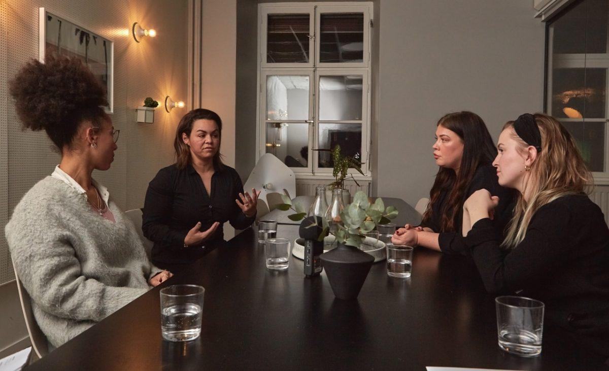 4 kvinnor pratar runt bord